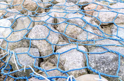 Cobblestone into lattice made of blue wire Royalty Free Stock Photos