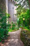 Cobblestone path with street light lamp near wall of stone brick medieval castle tower in green park in Republic San Marino. Cobblestone path with street light stock photography