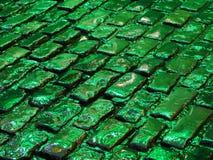 Cobblestone pavement lit by green light stock image