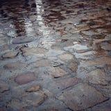 Cobblestone pavement in rainy day - retro filter. Wet paving stones. Stock Photos