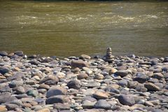 A cobblestone pyramid assembled on the rocky shore of the swift mountain river Katun royalty free stock photo