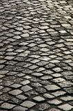 A cobblestone road. The old area paved by grey granite cobble-stones of the rough form Stock Image