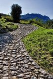Cobblestone road. Winding cobblestone road going up to the mountains royalty free stock photo