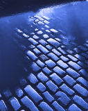 Cobblestone road in blue. Cobblestone road after rainfall back lit in blue Royalty Free Stock Image