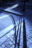 Cobblestone road shadow. Shadow of a fence projected on a blue cobblestone road Royalty Free Stock Photos