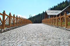 Cobblestone road with wooden fence Stock Images