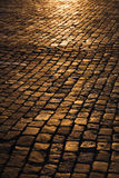 Cobblestone Street. High angle view of a cobblestone street at night with street lights reflecting off the surface. Vertical shot stock image