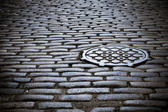 Cobblestone street. And manhole cover in old new york city street Royalty Free Stock Image