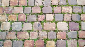 Cobblestone street with grass between the stones, texture or background Royalty Free Stock Photo