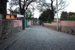 Cobblestone street in Huasca de Ocampo. Huasca de Ocampo, Hidalgo, Mexico - 2019: A typical cobblestone street at the town center royalty free stock image