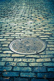 Cobblestone Street and Manhole. Old cobblestone street with vintage tone filter effect stock images