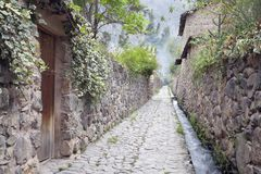 Cobblestone street in old Inca town in Sacred Valley. Atmospheric narrow cobblestone street with adobe houses, water channel running against wall in historic stock image