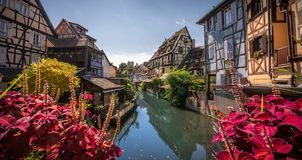 Cobblestone street in picturesque Alsace village with half timbered houses and beautiful flowers. royalty free stock photos