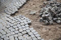 Cobblestone street repair. Details of ongoing construction work to repair a cobblestone road or street stock photos