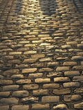 COBBLESTONE STREET AT SUNSET. Close up of cobblestone street illuminated by setting sun Stock Images