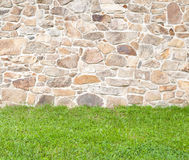 Cobblestone wall. Old brown and gray cobblestone wall with grass in the foreground royalty free stock image