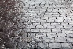 Cobblestones on pavement background, stone sidewalk texture gray or black color, wet bricks road surface pattern top view close up stock photos