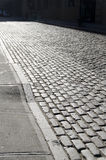 Cobblestones. Street at dawn leading into darkness Stock Photography