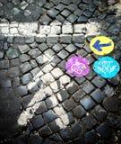 Cobblstone-Straße mit farbigen Anzeichen Stockfotos