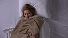 Coberta da mulher com a cobertura que encontra-se na cama, febre de sentimento, sintomas do frio vídeos de arquivo