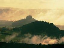 A coberta da névoa e da névoa da manhã ajardina abaixo dos picos de montanha Fotos de Stock Royalty Free