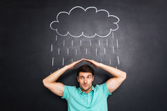 Coberta infeliz do homem novo da chuva tirada sobre o fundo do quadro imagem de stock