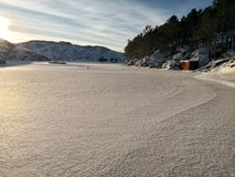 Coberto com a neve e o gelo, lago congelado, praia congelada, dia ensolarado em Noruega imagem de stock royalty free