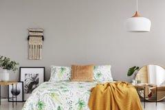 Cobertura alaranjada na edredão floral no quarto à moda interior com macramê feito a mão, os gráficos preto e branco e o espelho  fotografia de stock royalty free
