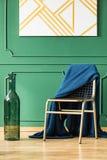 Cobertura azul na cadeira do ouro na sala de visitas mínima interior com vaso elegante e pintura abstrata branca e do ouro fotografia de stock