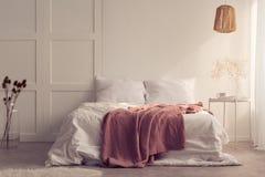 Cobertura cor-de-rosa na cama branca no interior mínimo do quarto com a tabela acima da lâmpada com planta imagem de stock