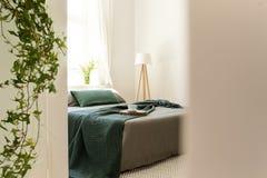 Cobertura e descansos verdes na cama cinzenta no interio mínimo do quarto foto de stock