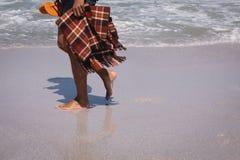 Cobertura e deslizador da terra arrendada do homem ao andar na praia na luz do sol fotos de stock