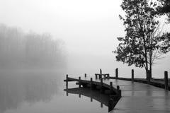 A cobertura grossa da névoa cobre o lago e a doca de madeira Fotografia de Stock