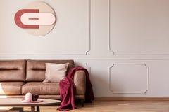 Cobertura vermelha e coxim cor-de-rosa no sofá no interior branco do apartamento com cartaz e tabela imagens de stock royalty free