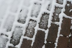 Coblestone covered by snow in the street. Closeup of coblestone covered by snow in the street Stock Photo