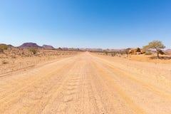 Cobrir o cruzamento de estrada 4x4 o deserto colorido em Twyfelfontein, no Damaraland majestoso Brandberg, destino cênico do curs Fotografia de Stock Royalty Free