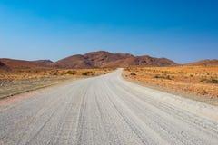 Cobrir o cruzamento de estrada 4x4 o deserto colorido em Twyfelfontein, no Damaraland majestoso Brandberg, destino cênico do curs Fotos de Stock Royalty Free
