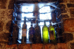 Cobweb covered wine bottles in wine cellar by the  Royalty Free Stock Photography