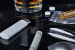 Cocaína, píldoras, alcohol y heroína en jeringuilla foto de archivo