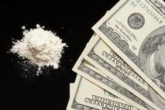 Cocaïne en honderden op zwarte achtergrond Stock Foto