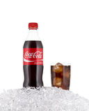 Coca cola bottle in a bed of ice. Coca cola bottle and a filled glass in a bed of ice royalty free stock photos