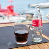 Coca-Cola bottle and a glass on the table of a beach bar. Of the city Vrsar in Croatia royalty free stock photography