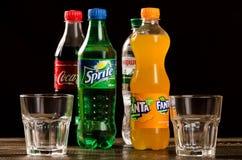 Coca-cola, Fanta, Sprite avec des verres sur un fond foncé Photographie stock libre de droits