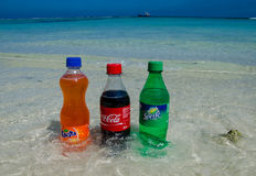 Coca-cola, fanta, sprite bottles on the beach Royalty Free Stock Photo