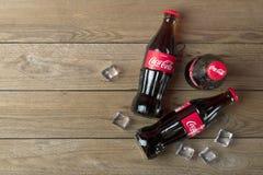 Coca-Cola-Flasche mit Eisw?rfeln auf h?lzernem Hintergrund stockbilder