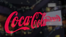 Coca-Cola logo on the glass against blurred business center. Editorial 3D rendering Stock Image
