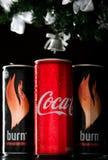 Coca - cola och två brännskador för nytt år och jul på en svart bakgrund Coca - cola och brännskadan är royaltyfria bilder