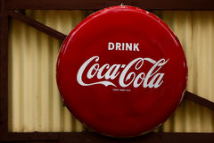 Coca-Cola sign. A Coca-Cola red circular sign, hanging on a brown metal and wooden background Royalty Free Stock Photos