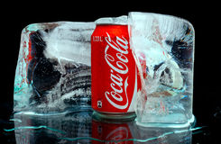 Coca cola. ZAGREB , CROATIA - JANUARY 24 ,2014 :   coca-cola can splashed with water in block of ice on black background, product shot Stock Image