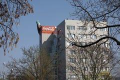 Coca - colabyggnad med solen som skiner på företagslogo arkivbild